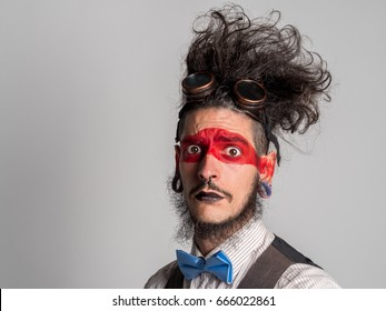 Portrait of a handsome theatrical actor with a mime make-up and a piercing in his nose. Different person concept