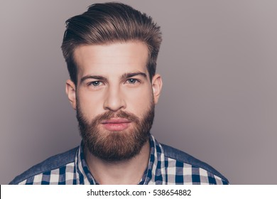 portrait of handsome thinking young man looking at camera isolatet on gray wall