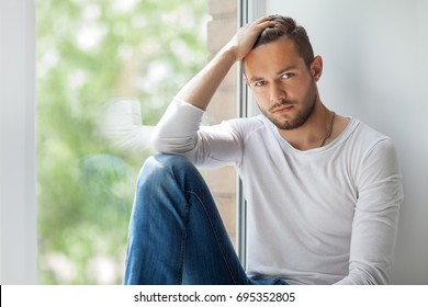 Portrait of handsome thoughtful man touching his hair relaxing on window sill