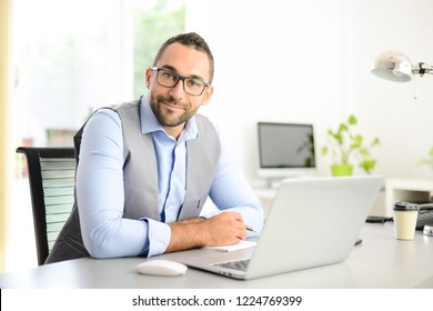 portrait of handsome trendy casual mid age business man in office desk with laptop computer