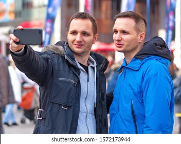 Portrait of the handsome twin guys in the city taking selfie withe the mobile phone