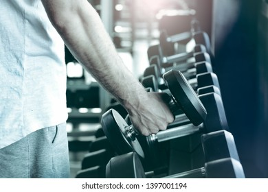 Portrait of handsome weightlifter athletic man during workout with dumbbell power exercise in gym. Fitness man with dumbbell in sport club. Sport, exercise, fitness concept.