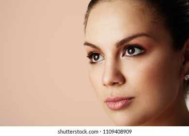 Portrait of handsome woman with big brown eyes and dark eyebrows looking away over empty color studio background.Model with light nude make-up.Copy paste space,close up.Healthcare skin concept