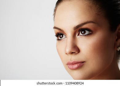 Portrait of handsome woman with big brown eyes and dark eyebrows looking away over empty studio background.Model with light nude make-up.Copy paste space,close up.Healthcare skin concept