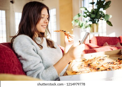 Portrait of handsome woman eating pizza at home and taking photo of her food to share memory