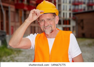 portrait of handsome worker in his 50s with helmet standing outside