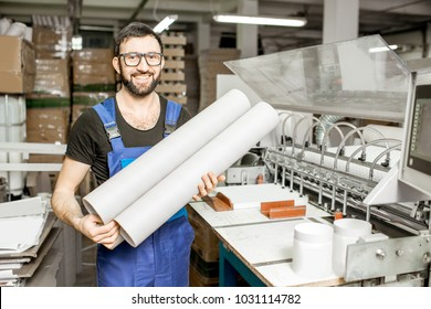 Portrait of a handsome worker in unifrom standing with paper tubes at the old printing manufacturing