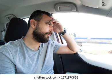 Portrait of handsome worried man driving car
