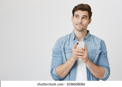 Portrait of handsome young adult with dreamy look, thinking while holding smartphone, isolated over white background. Son tries to made up message for his father, explaining why he took car