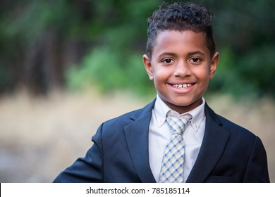 Portrait of a handsome young African American boy in formal clothing. Smiling with his arms folded and wearing a suit and tie