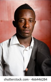 Portrait of handsome young African businessman outdoors at night