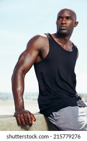 Portrait of handsome young african male model looking away. Muscular young man outdoors.