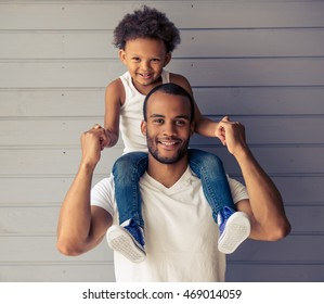Portrait of handsome young Afro American father and his cute child looking at camera and smiling. Kid is sitting on father's shoulders