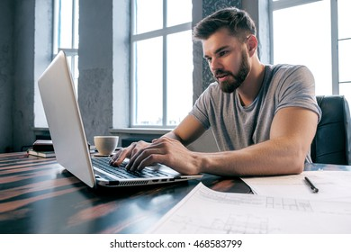 Portrait of handsome young architect using laptop at desk in office