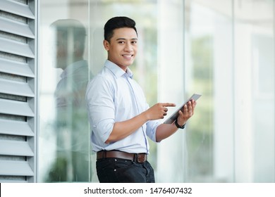Portrait of handsome young Asian businessman standing outside the office building and ucing aplication on tablet computer - Shutterstock ID 1476407432