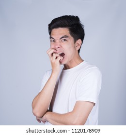 Portrait handsome young asian man wearing a white T-shirt stressed and anxiety isolated on grey background. Asian man people. business success concept.