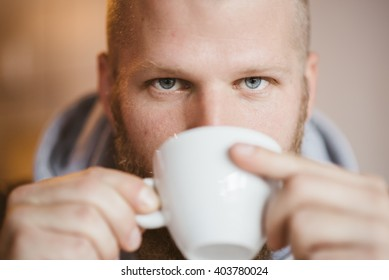 portrait of handsome young bearded man drinking coffee
