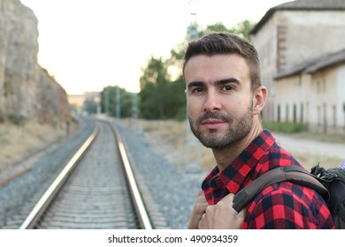 Portrait of handsome young bearded man waiting for train on railway station in the European countryside