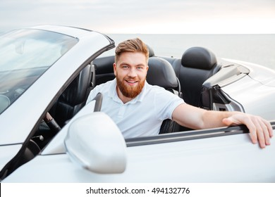 Portrait of a handsome young bearded man getting into his car