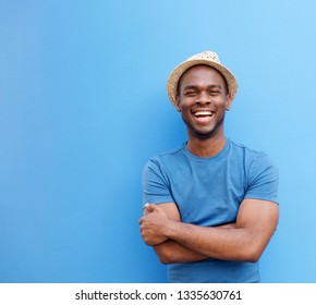 Portrait of handsome young black guy with hat smiling against blue background