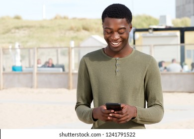 Portrait of handsome young black man looking at mobile phone