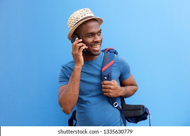 Portrait of handsome young black man with bag talking on cellphone against blue background