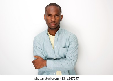 Portrait of handsome young black man with arms folded by white background