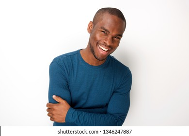 Portrait of handsome young black man smiling with arms folded by white background