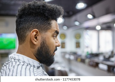 Portrait of handsome young black with unshaven beard sitting covered with blanket in barbershop waiting for barber to cut him new haircut and trim mustach hair.Male beauty treatment concept