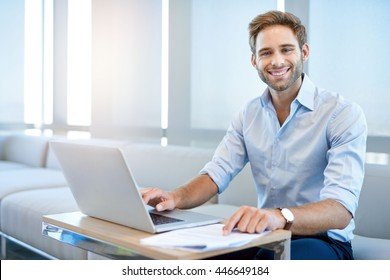 Portrait of a handsome young business entrepreneur, sitting in a modern business lounge and smiling at the camera with his laptop open in front of him