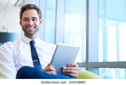 Portrait of a handsome young business executive sitting next to large windows in a modern office holding a digital tablet and smiling broadly at the camera