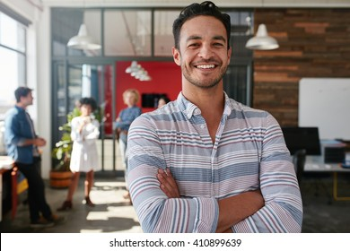 Portrait of a handsome young business man standing with arms crossed in an office. Smart caucasian young male designer with his colleagues in background.