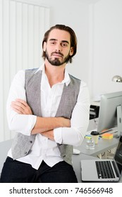 portrait of a handsome young business man with beard and long hair wearing casual wear in office