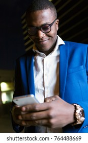 Portrait of handsome young business man using his mobile phone in the street at night.