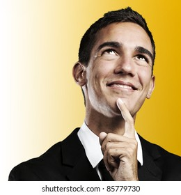portrait of handsome young business man thinking and looking up against a yellow background