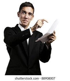 portrait of a handsome young business man pointing a contract over white background