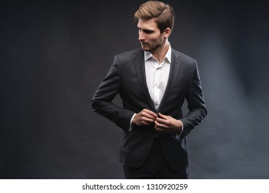 Portrait of a handsome young businessman dressed in suit isolated over gray background