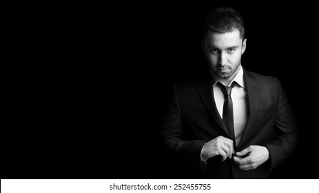 Portrait of handsome and young businessman on black background. Black and white