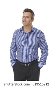 Portrait of handsome young businessman in shirt and trousers standing with hands in pockets.