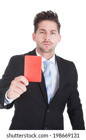 Portrait of handsome young businessman showing red card over white background