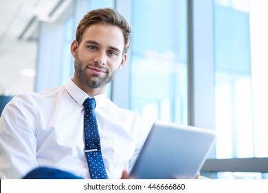 Portrait of a handsome young businessman sitting alongside large windows in a modern office space looking at the camera while holding a digital tablet and smiling