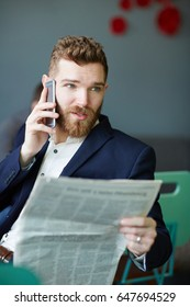 Portrait of handsome young businessman speaking by phone smartphone and reading morning newspaper  in cafe