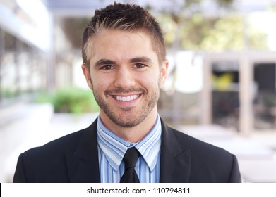 portrait of a handsome young businessman standing outside office