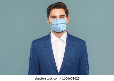 Portrait of handsome young businessman with surgical medical mask looking at camera. Business people medicine and health care concept. Indoor, studio shot on blue background