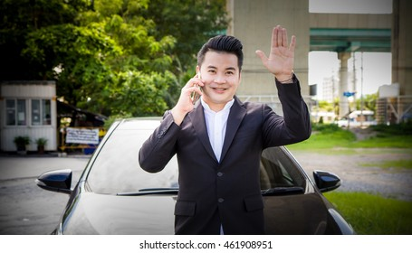 Portrait of a handsome Young businessman waving his to someone.