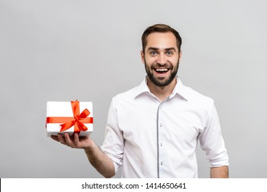 Portrait of a handsome young businessman wearing white shirt and tie standing isolated over gray background, showing gift box