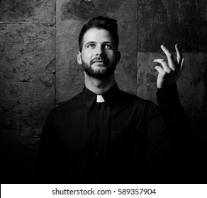 Portrait of handsome young catholic priest preaching looking up smiling. Black and white photo.