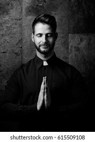 Portrait of handsome young catholic priest praying with closed eyes. Black and white photo.