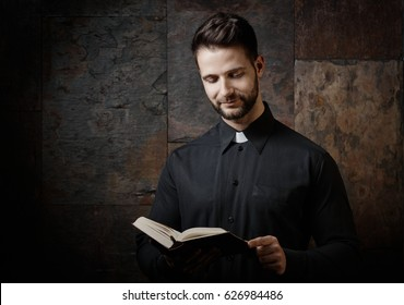 Portrait of handsome young catholic priest reading the prayer book against dark background.