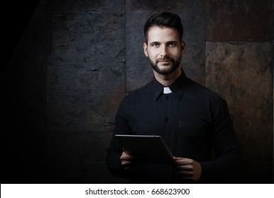 Portrait of handsome young catholic priest using tablet against dark background.